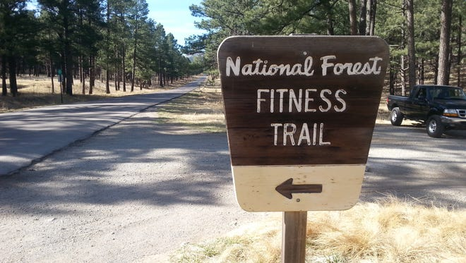 A sign marks the entrance to a fitness trail on Cedar Creek Drive in the Smokey Bear Ranger District of the Lincoln National Forest.