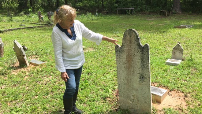 Tallahassee resident Nita Davis reads the gravestone of her great, great, great grandfather, Ansel Ferrell, a Revolutionary War veteran who settled in Leon County and is buried in a family cemetery.