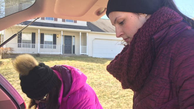 Savannah Kirby, 16, gets ready to scoop dog poop from a yard in her hometown of Stewartstown on Friday with her mom, Alana. The 16-year-old goes around to her neighbor's yards and scoops up their dog poop, charging a flat monthly rate.