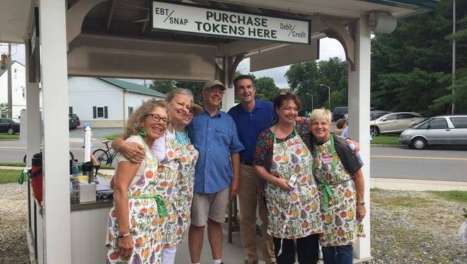 Gov. Ralph Northam poses with Onancock Market workers during a visit to the market in Onancock, Virginia to kick off Virginia Farmer's Market Week on Saturday, July 28, 2018.