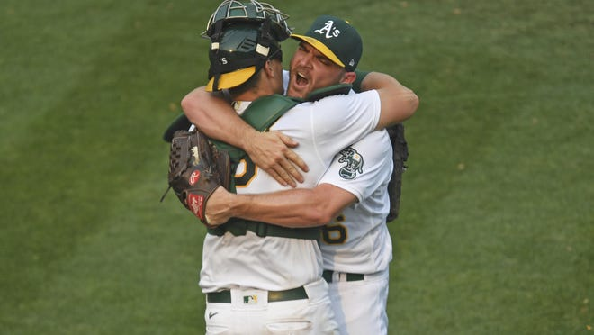 Oakland Athletics pitcher Liam Hendriks (16) celebrates with catcher Sean Murphy (12) on Thursday after striking out Chicago White Sox hitter Nomar Mazara (30) for the final out in the ninth inning of Game 3 of the American League Wild Card Round at the Coliseum in Oakland, Calif. The A's defeated the Chicago White Sox 6-4.