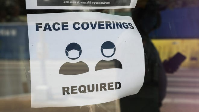 A visitor wearing a mask to protect against the spread of COVID-19 passes a sign requiring masks, Tuesday, July 7, 2020, in San Antonio.