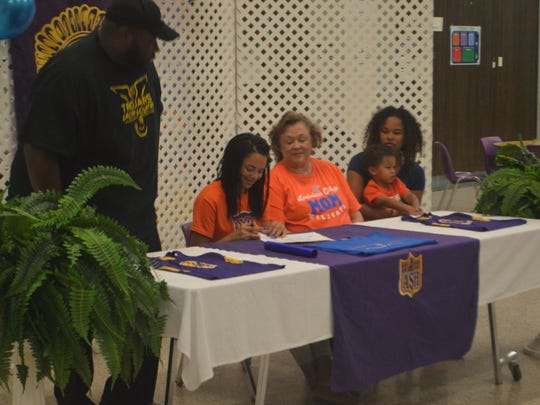 ASH track athlete Christine Seibles (second left) signs a celebratory form with Louisiana College Wednesday.
