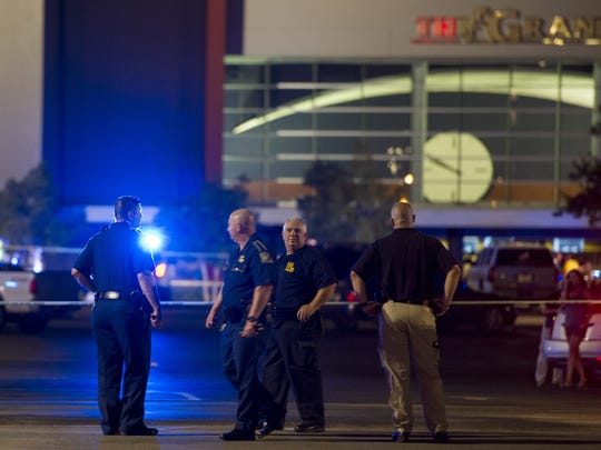 Law enforcement personnel stand near a police line at The Grand Theatre following a deadly shooting in Lafayette Thursday.
