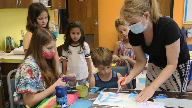 Local artist Sherry Jones, right, works with Community School of the Arts students creating a collage from tissue paper, Monday, July 20, 2020, during the first day of the