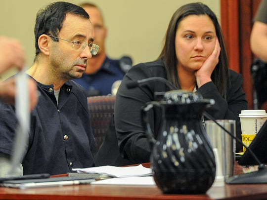 Former sports doctor Larry Nassar sits with one of his attorney's Molly Blythe at his sentencing Wednesday, Jan. 24, 2018 in Lansing, Michigan.