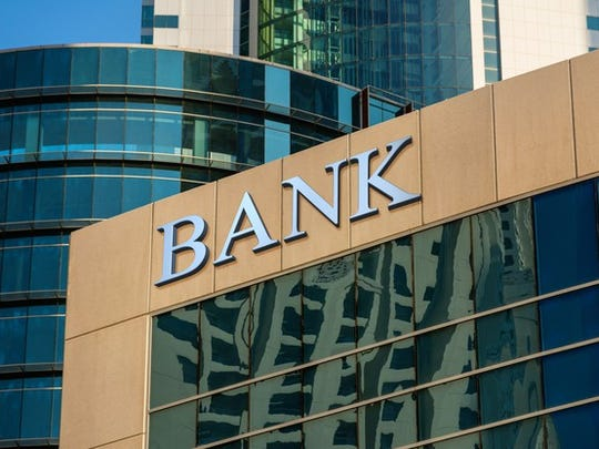 """A larger glass panel building with the word """"bank"""" at the top."""