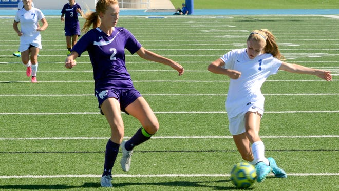 Carlsbad's Rylee Hoover passes the ball into the box against Clovis' Jaci Sievers on Sept. 26, 2015. The Cavegirls will host the Wildcats in the first round of this year's 6A state tournament.