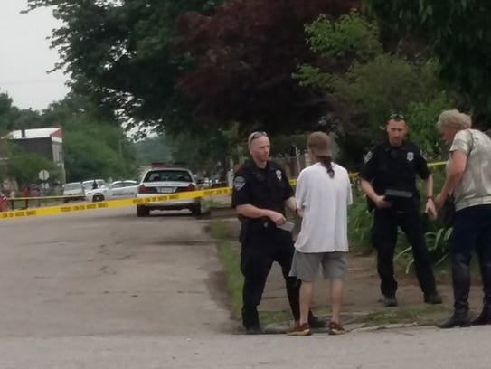 Officers with Evansville Police Department talk to witnesses at the scene of a shooting that occurred in the 1100 block of West Delaware Street Friday evening.
