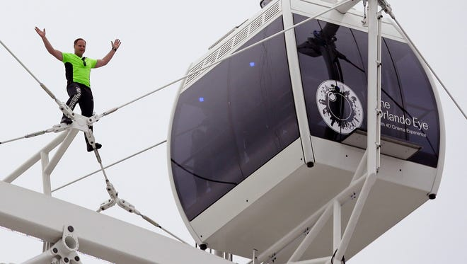Nik Wallenda waves to the crowd below after he walked untethered along the rim of the Orlando Eye, the city's new 400-foot observation wheel, on April 29, 2015.