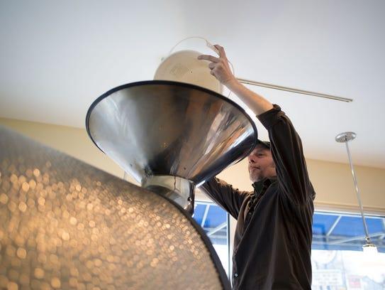 Roaster Sean Hixon loads in a bucket of coffee beans