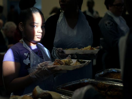 A young girl loads up her plate as Bethele Development