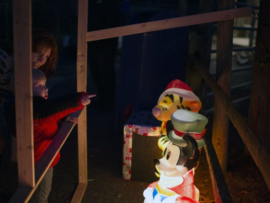A young boy points out Disney themed Christmas decorations