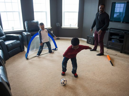Chase Merriweather, 5, front, plays soccer with his