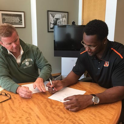 Michael Johnson signs his Bengals contract alongside