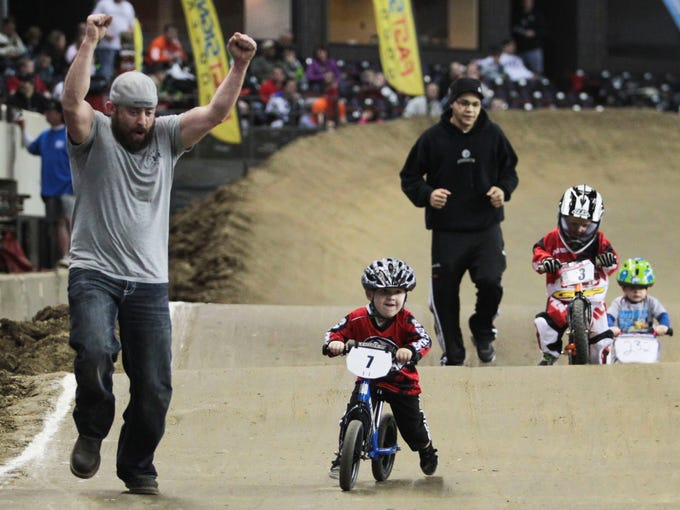 Eli Boland roots on son Brody Walters in the Strider Class of the USA BMX Bluegrass Nationals at Freedom Hall Saturday morning. Racers' age range from two to over 70 years old. More than 250 races took place on Saturday.