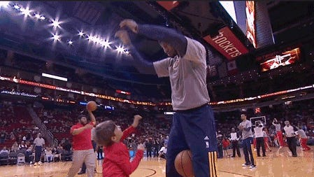 Screenshot of Paul George playing around with a kid during pregame warmups.