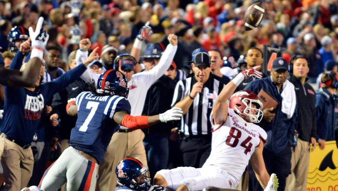 Arkansas Razorbacks tight end Hunter Henry (84) laterals the ball as he is tackled by Mississippi Rebels defensive back Tony Bridges (1) during overtime at Vaught-Hemingway Stadium. Arkansas won 53-52.