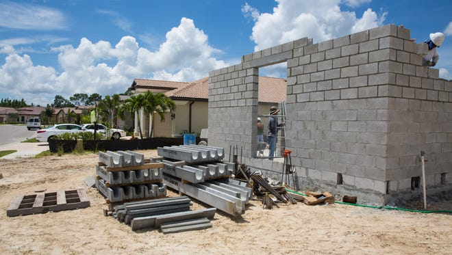 Constructions workers build the framework for a new home at the Bonita Lakes community in Bonita Springs on Aug. 25, 2016.