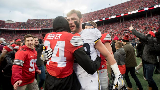 Michigan tight end Jake Butt gets a hug from Ohio State safety Malik Hooker as they walk off the field at the end of the game.