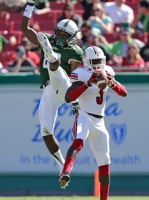 Louisville cornerback Charles Gaines intercepts a pass intended for South Florida wide receiver Deonte Welch before returning it 70 yards for a touchdown last October.