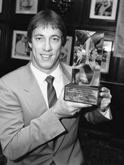Jim Kelly holds the trophy given to him, on July 17, 1984, in New York by the Professional Football Writers of America for being voted the most valuable player of the United States Football League 1984 season. Kelly led the expansion Gamblers to a 13-5 record.
