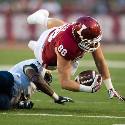 Indiana tight end Anthony Corsaro (88) is brought down by Navy cornerback Parrish Gaines (2) during the second half of a game Sept. 7, 2013, in Bloomington, Ind.