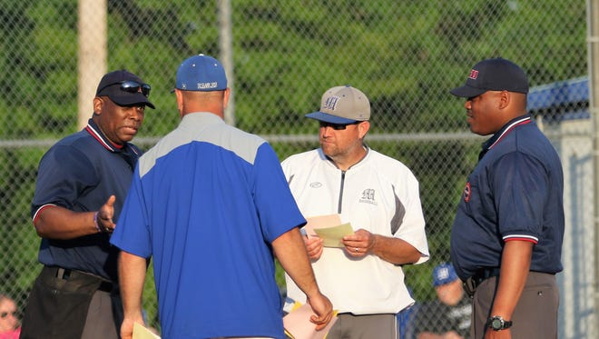 Chester County coach Mike Goff and McNairy Central coach Brian Franks meet with the umpires before the Bobcats' 6-4 win in the District 14-AA tournament on May 8, 2018.