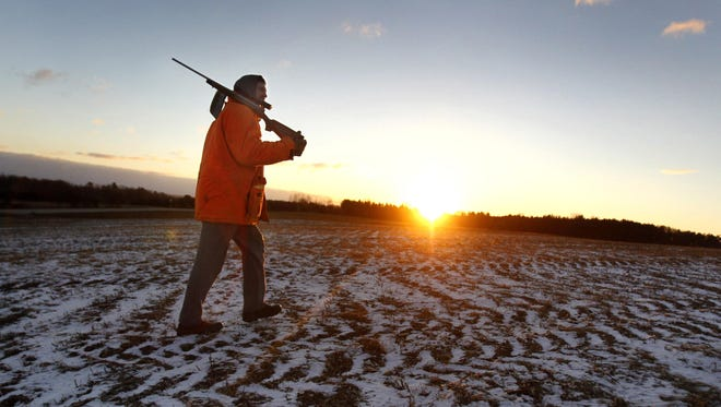 Jeff Peters crosses a frozen cornfield at sunrise on the way join his son in their deer stand on the opening day of deer hunting season Nov. 23, 2013 near Shiocton.