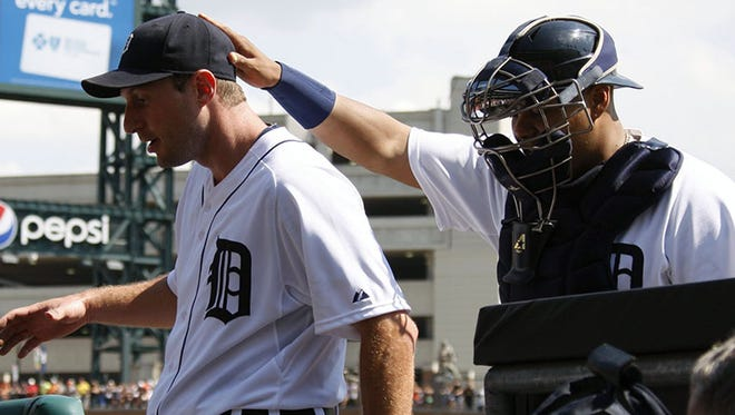 Tigers pitcher Max Scherzer and catcher Brayan Pena going into the dugout at Comerica Park on Aug. 17, 2013.