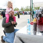 Mark Kogler asks his daughter Summer what she'd like to sample from Task Force BBQ sauce Saturday, April 18, 2015 at the Drake Road Farmers Market in Fort Collins, CO.
