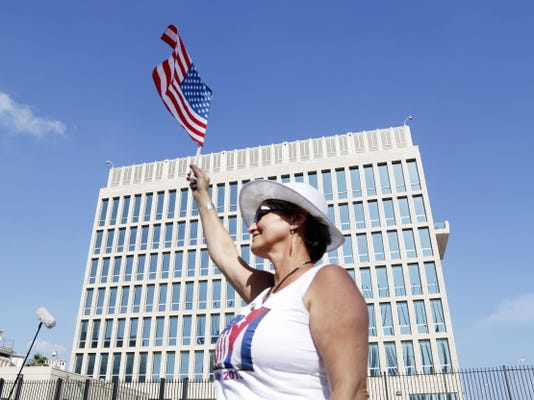 Cuban-American Gina Gonzalez waves an American flag in front of the United States embassy in Havana, Cuba, Monday, July 20, 2015.  The U.S. and Cuba restored full diplomatic relations Monday after more than five decades of frosty relations rooted in the Cold War.