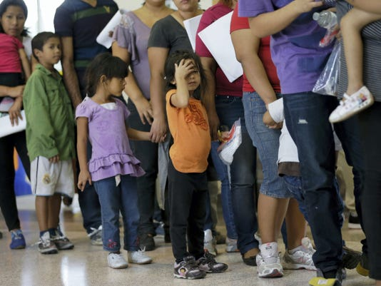 FILE - In this June 20, 2014, file photo, immigrants who entered the U.S. illegally stand in line for tickets at the bus station after they were released from a U.S. Customs and Border Protection processing facility in McAllen, Texas. Hundreds of families and children from Central America caught traveling alone in recent weeks across the Mexican border told U.S. immigration agents they made the dangerous journey in part because they believe they will be permitted to stay in the United States and collect public benefits, according to internal intelligence files from the Homeland Security Department. (AP Photo/Eric Gay, File)