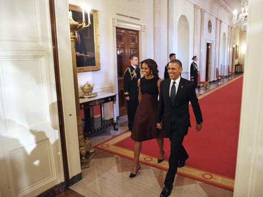 US President Barack Obama and First Lady Michelle Obama arrive for the Presidential Medal of Freedom presentation ceremony in the East Room of the White House on November 20, 2013 in Washington, DC.  The Medal of Freedom is the country's foremost civilian honor.