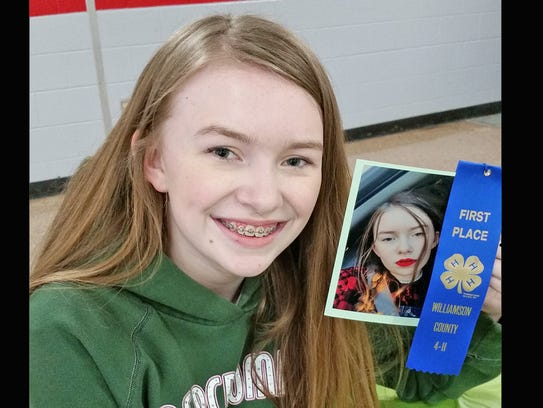 Leah Kennedy displays her blue ribbon and winning photo