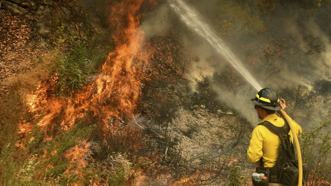 A firefighter puts out a hot spot along Highway 38 northwest of Forrest Falls as the El Dorado Fire continues to burn Thursday afternoon Sept. 10, 2020. The fire is into its sixth after being started by a device at a gender reveal party last week.