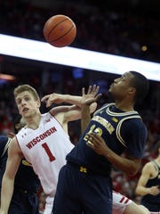 Wisconsin guard Brevin Pritzl (1) and Michigan guard Muhammad-Ali Abdur-Rahkman (12) look for the rebound in Michigan's 83-72 win on Sunday, Feb. 11, 2018, in Madison, Wis.