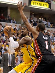 Indiana Pacers center Roy Hibbert gets the ball in the post in front of Miami Heat forward Chris Bosh.