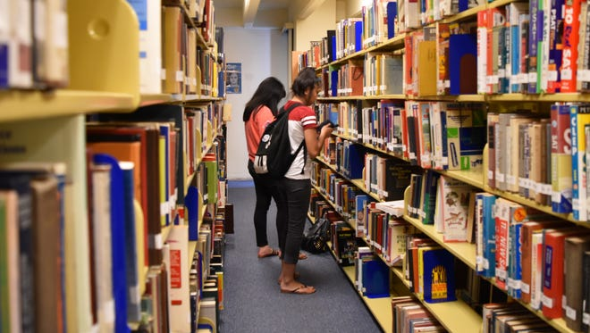 Library patrons look through an aisle of books at the Nieves M. Flores Memorial Public Library on April 10, 2017.