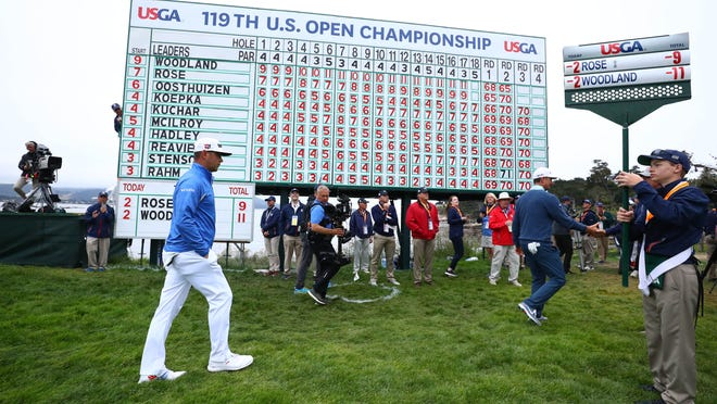Leader Gary Woodland walks past the leaderboard on the 18th green during the third round of the 2019 U.S. Open. Photo: Rob Schumacher/USA TODAY Sports