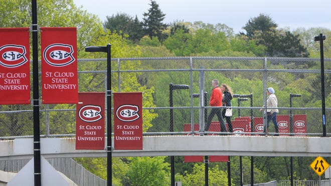People cross University Drive over a pedestrian bridge Tuesday at St. Cloud State University.