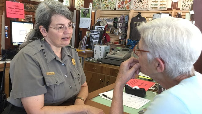 Tricia Ford, left, the fee program manager at Whiskeytown National Recreation Area, explains the features of a lifetime senior pass to Jackie Reynolds of Palo Cedro. Reynolds bought one of the passes Thursday at the Whiskeytown Visitors Center.