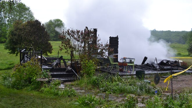 Smoking remains of a home at 1329 Old Stage Road in Westford are seen in this photo taken Thursday, June 7, 2018. The homeowner has been charged with first-degree arson.