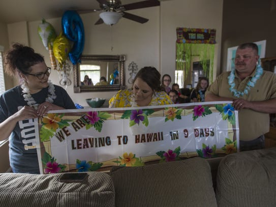 Ceene Brazlovitz (center), with the help of her parents, Jennifer and Reid Brinton, holds a sign to surprise her son, Bentley Brazlovitz. His wish to go to Hawaii was granted on March 24, 2018, in their Gilbert home. Bentley is nearing one year in remission after battling embryonal rhabdomyosarcoma, a soft tissue cancer. Johanna Huckeba/azcentral