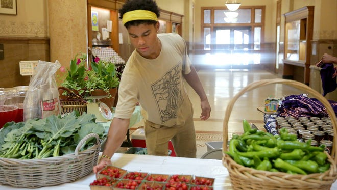 Benjamin Johnson, 18, a Marquette University High School graduate, sets out fresh cherries at a farmers market at Milwaukee City Hall.