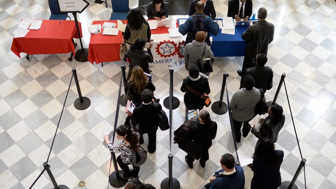 Job seekers wait to speak with employers at a job fair in New York.