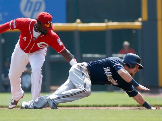 Milwaukee's Scooter Gennett is tagged out by Reds second baseman Brandon Phillips after Gennett was caught off base in the first inning.