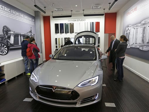 Customers check out a new Tesla all electric car, Monday,