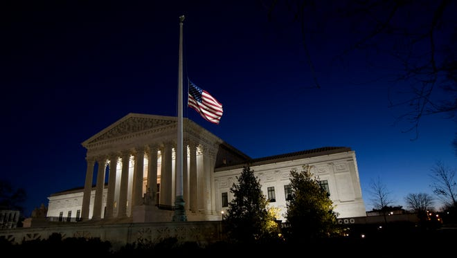 An American flag flies at half-staff in front of the Supreme Court building in honor of Justice Antonin Scalia on Feb. 14, 2016.