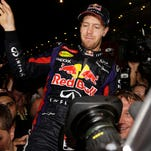Red Bull driver Sebastian Vettel is held aloft by his teammates in pit lane after winning the Indian Formula One Grand Prix and his 4th straight Formula 1 championship.